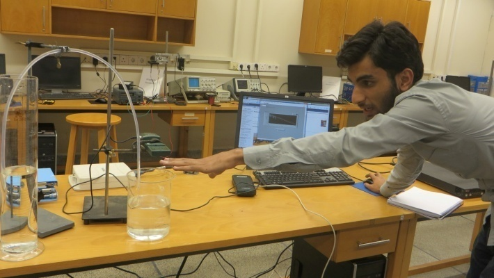 Qamar uses an ultrasonic sensor to study the dynamics of water flow in a siphon.